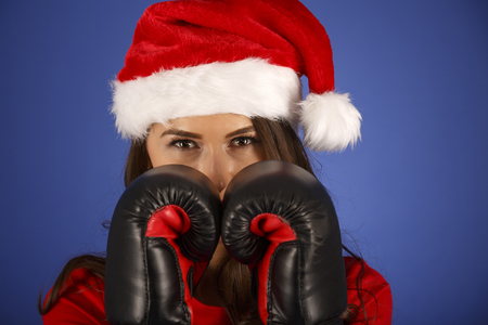 Christmas girl with Santa Claus clothes and boxing glove isolated on blue background