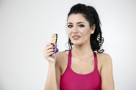 comiendo cereal: diet sporty young woman eating cereal bar Foto de archivo