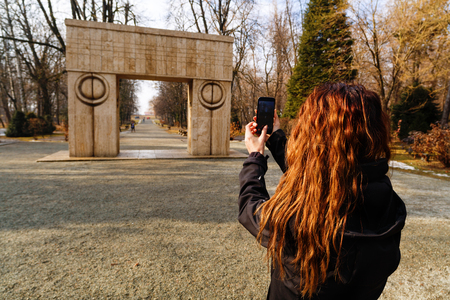 constantin: woman tourist traveling through Romania. Targu Jiu, kissing gate