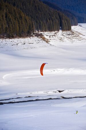 kiting: people doing kitesurfing on a frozen mountain lake