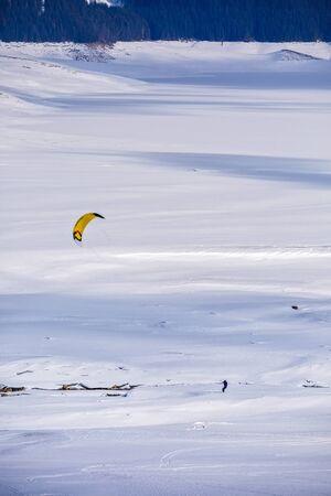 kite surfing: people doing kitesurfing on a frozen mountain lake