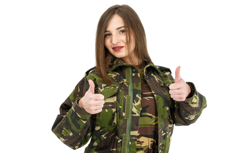 young woman soldier in military camouflage outfit showing peace sign, ok Foto de archivo