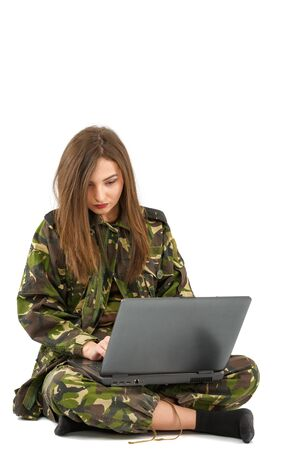 young woman soldier in camouflage outfit with a laptop Stock Photo