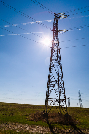 electricity pylons on a farm field Stock Photo