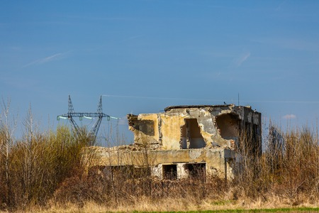 ruins of abandoned buildings surrounded by vegetation Stock Photo