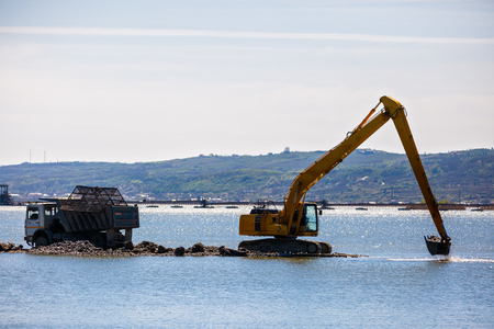 an excavator loads a dump sand in the water