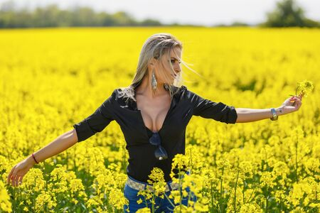Portrait with a beautiful woman in rapeseed
