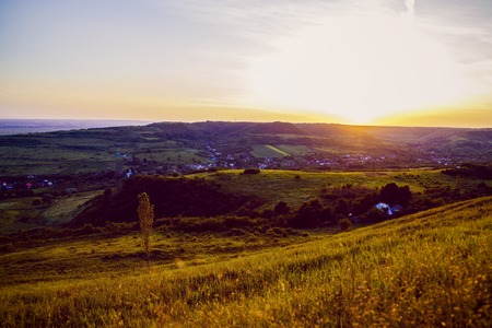 vibrance: Sunset over a hill to the country in Romania