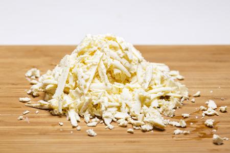 Formaggio mozzarella tagliuzzato su un tagliere con una grattugia