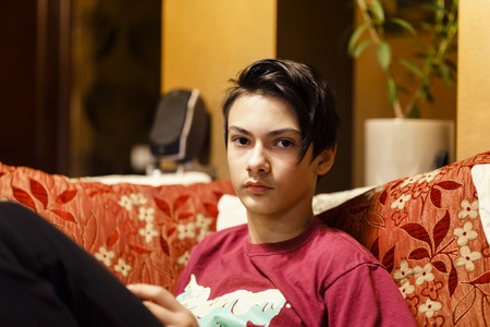 a boy sitting on the couch and playing Stock Photo