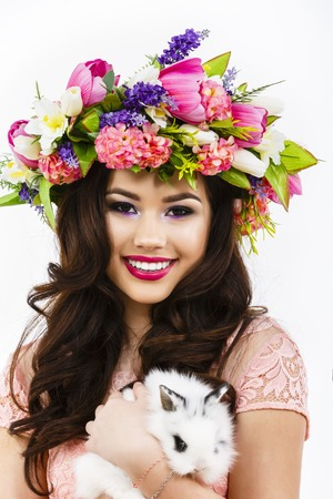 Beautiful young woman with a white rabbit in her hand, easter concept,