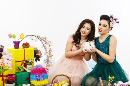 Two beautiful women playing in easter decoration with a rabbit. makeup and special hairstyle for holidays