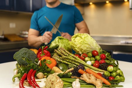 Man with a large variety of vegetables, ready to be cooked