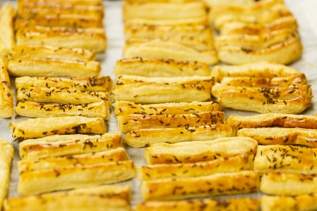 Closeup of a tray with freshly baked cheese crackers with caraway seeds