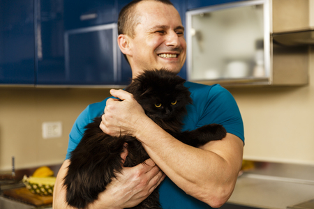 Closeup of a man holding his adorable furry black cat Stock Photo