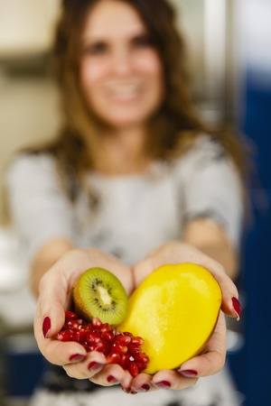 Woman offering exotic fruits, her face is in blurred background