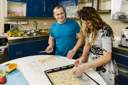 Couple cooking cheese crackers with seeds at home Stock Photo