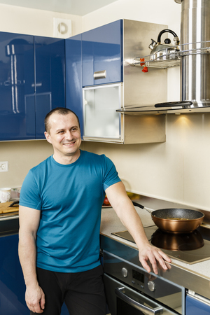 Happy man standing in his kitchen, leaning on the stove Stock Photo