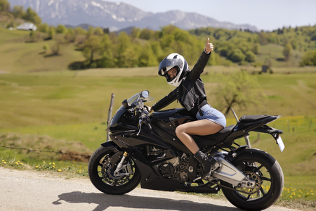 Beautiful woman driving a motorcycle on a mountain road 免版税图像