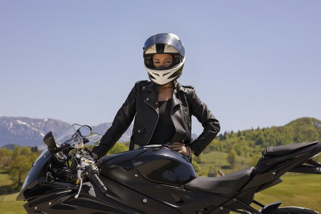 Beautiful woman posing with a motorcycle in mountain scenery Фото со стока