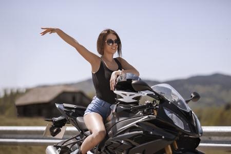 Beautiful woman posing with a motorcycle in mountain scenery Standard-Bild