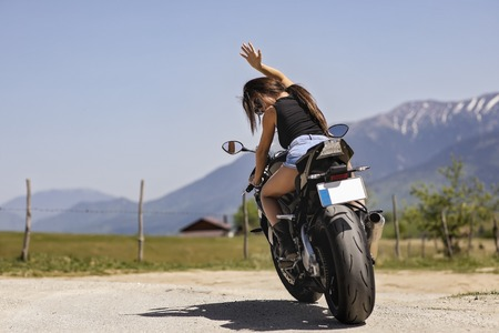 Beautiful woman driving a motorcycle on a mountain road Standard-Bild