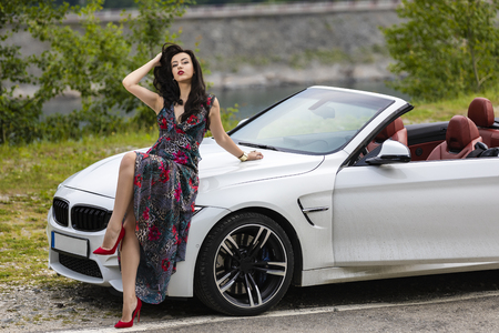 Fashion portrait of young woman in elegant dress outdoor near a convertible car