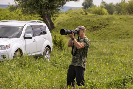 A bird watcher and bird photographer with a large telephoto lens, in a field