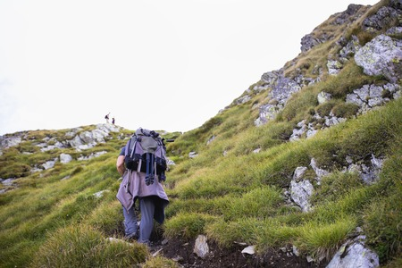 Photographer with backpack and camera hiking on a mountain trail