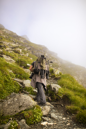 Photographer with backpack and camera hiking on a mountain trail 免版税图像 - 105977609
