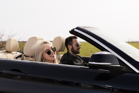 beautiful young couple traveling in a convertible Stock Photo