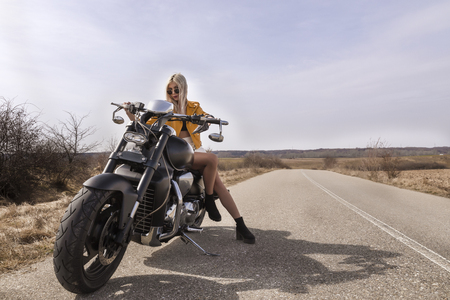 A beautiful young woman sitting on a black and chrome motorbike