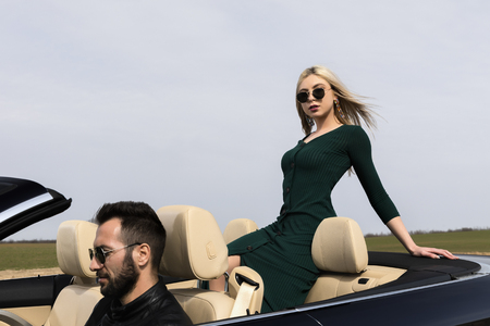 beautiful young couple traveling in a convertible