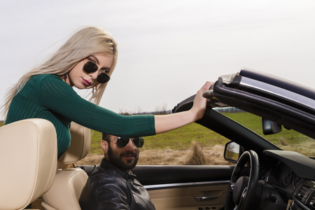 beautiful young couple traveling in a convertible Archivio Fotografico