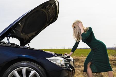Junge Frau mit Absätzen, die ihr kaputtes Auto repariert