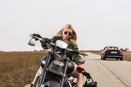 Una bellissima giovane donna seduta su una moto nera e cromata Archivio Fotografico