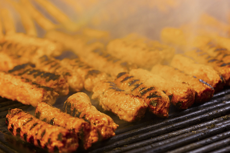 Meat rolls (mititei, mici) on the grill which is a traditional Balcanic (Romanian) dish