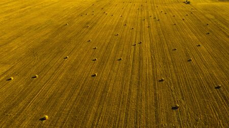 Aerial View Over Rural Landscape. Hay Bales In A Farm Field On A Sunny Day