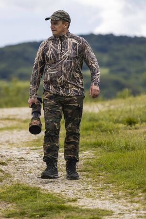 Professional wildlife photographer in camouflage clothing Stock Photo