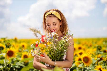 Pretty young woman on a sunflowers field Standard-Bild