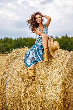 Beautiful cowboy woman Posing near at the haystacks, Fashion concept.