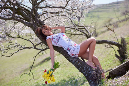 A beautiful woman with a bouquet of flowers poses in nature during the spring