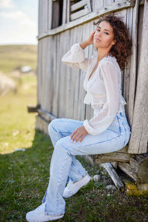A beautiful woman with curly hair poses near an old wooden house. fashion style. Stok Fotoğraf