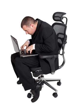 workaholic: Funny businessman sitting and working on laptop  Isolated on white background