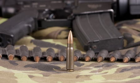 bullet belt ammunition and one single round, camouflage background photo