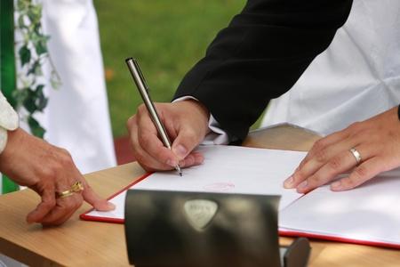 Wedding day - groom make the signature Stock Photo