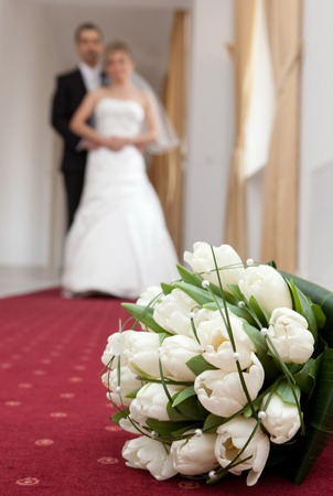 Wedding detail of the bouquet, bride and groom in background photo