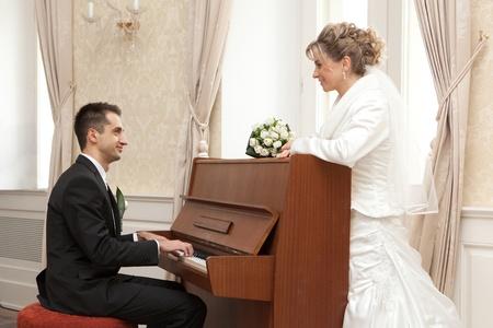 Groom playing piano  Happy bride   photo