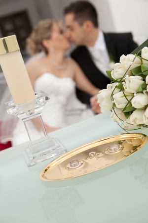 Wedding detail of the rings and bouquet  Kiss in background  photo