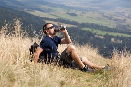 rest day: sportive man on the mountain trek, man sit and rest